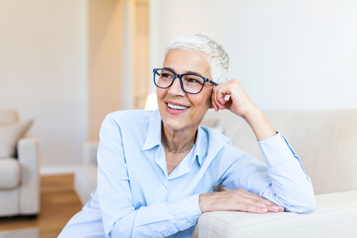 An elderly woman smiling with glasses